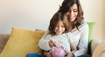 parent and child putting money in a savings bank