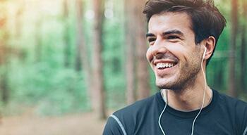 man in forest smiling with headphones in