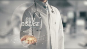 "Dentist holding a sign that says, ""Gum Disease"""