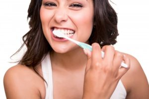 woman smiling brushing her teeth