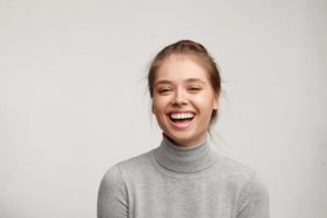 woman in gray turtleneck sweater smiling